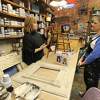 Bev Crosson, left, owner of Farmhouse gives a painting lesson to Mandy Jackson at her store on West Main Street in Tupelo.