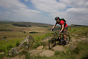 Cyclist descends footpath suffering from erosion beneath Stanage Edge gritstone cliffs, Peak District National Park, Derbyshire..Located in the Peak District National Park in England Stanage Edge is the largest of the gritstone edges that overlook Hathersage in Derbyshire. Stanage Edge at approximately 4 miles in length and 458m at its highest point is the largest of the gritstone cliffs that overlook Hathersage, Derbyshire. The area is one of the most popular locations in the Peak District National Park for climbing and walking with hundreds of rock climbing routes to challenge all ranges of ability. Walkers are drawn to the area to enjoy the varied moorland scenery with stunning views across the surrounding countryside including Hathersage, Castleton and the 'Shivering Mountain', Mam Tor in the west. A walk along the edge is an easy route but the exposed cliff can make conditions difficult throughout the year as it is often battered by wind, rain and regular snowfall in the winter months. There are a number of popular walks including routes along the remains of a Roman Road and towards Redmires Reservoir to the east as well as longer walks such as those including the nearby Longshaw Estate. Sopurce http://www.stanageedge.co.uk