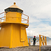 Boy fishing next to a lighthouse on the waterfront in Reykjavik, Iceland