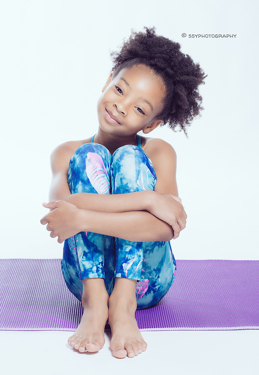 Little African American girl doing yoga on a purple yoga mat.