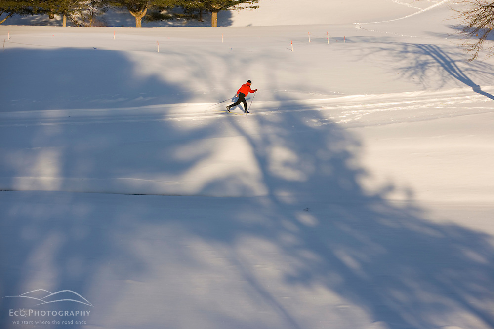 A man cross-country skiing (track skiing) on a groomed trail next to the frozen Ottauquechee River in Quechee, Vermont.