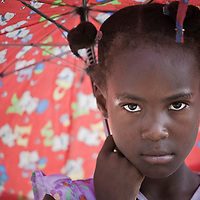 A girl shades from the heat of the midday sun on Ile de la Gonave, Haiti