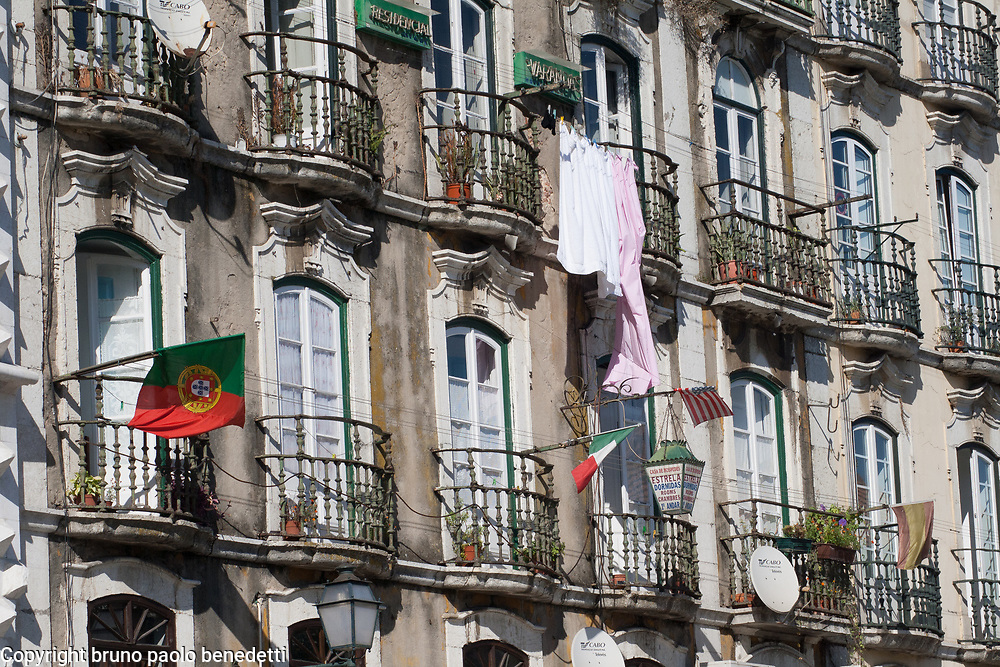 lisbon house facade with flags and hang clothes