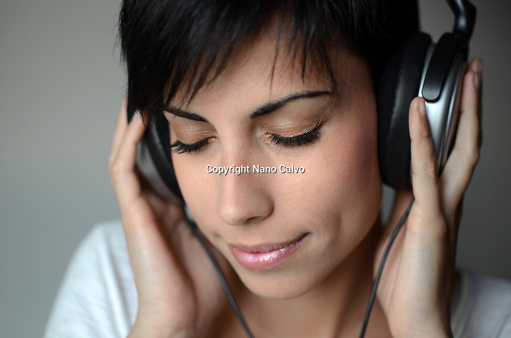 Young attractive woman, with short hair, listening to music with headphones