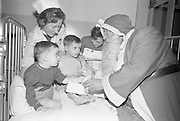 Christy Doran of Dublin and Bernard Cawley, a Traveller, sit wide-eyed as Santa gives them presents at the Prescott Christmas Party at St. Marys Orthapedic Hospital, Baldoyle, Dublin..13.12.1962