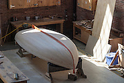 Unfinished wooden boat on jacks in boatbuilder's workshop