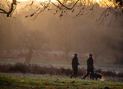 © Licensed to London News Pictures. 11/12/2019. London, UK. Walkers were greeted with an orange sunrise over Richmond Park this morning as  weather experts predict more wind, rain and showers for voters in tomorrow's General Election on Thursday 12th December 2019. Photo credit: Alex Lentati/LNP