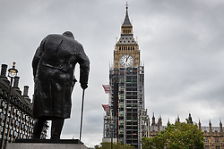 © Licensed to London News Pictures. 10/10/2017. Winston Churchill's statue looks on from Parliament Square as workers erect 96 meters of scaffolding up to the clock face of The Elizabeth Tower - home of the Big Ben bell at The Houses of Parliament.  The work is part of a three-year programme to conserve the Great Clock, the tower and Big Ben. London, UK. Photo credit: Peter Macdiarmid/LNP
