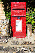 Post Office postbox in an old dry stone wall at Swinbrook in the Cotswolds, England, UK