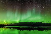 Aurora borealis over Chugach Mountains reflected in a pond near Knik River, Alaska