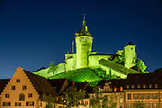 Munot Castle glows floodlit in green at night. The Munot, Schaffhausen's iconic circular fortress, was built by forced labor in 1564 after the religious wars of the Reformation. Switzerland, Europe.