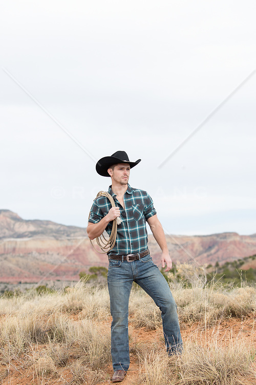 cowboy holding a lasso on a mountain top