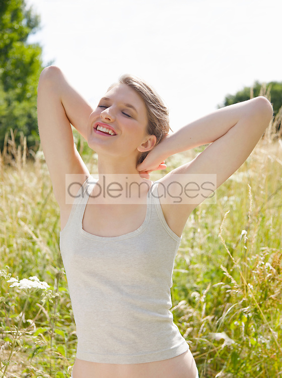 Smiling young woman standing in a field with eyes closed