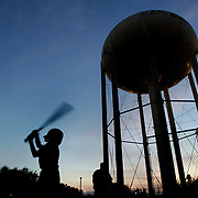 McAllen, TX / 2006 -  DeShaun Primus, 7, takes batting practice as the sun falls behind a water tower at Municipal Park in McAllen.  Photo by Mike Roy / The Monitor