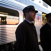 Conductors Victor Bennett and Larry Talley wait for passengers at dawn at Broad Run VRE station in Manassas, Virginia.