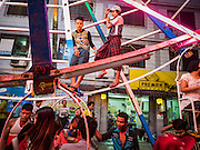 29 OCTOBER 2015 - YANGON, MYANMAR: Workers on a Ferris Wheel during a street carnival in central Yangon. Electricity is scarce in Myanmar, especially in rural areas, and most traveling carnivals use human powered rides. Workers climb to the top of the Ferris Wheel and then pull it around getting it spinning. They do the same with Merry Go Rounds, but instead of climbing to the top they pull it around. The carnival coincided with the Thadingyut Festival, the Lighting Festival of Myanmar, which is held on the full moon day of the Burmese Lunar month of Thadingyut, October or November on the Gregorian calendar. The carnival featured food, rides and games.      PHOTO BY JACK KURTZ