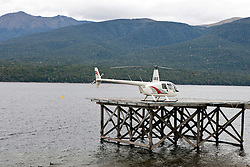 A helicopter sits on a dock with hills in the background, Lake Te Anau, South Island, New Zealand