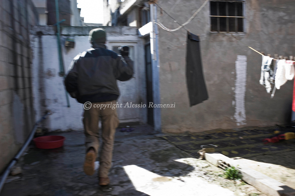 SYRIA - Al Qsair. A Syrian reporter as he is running away from an attack by Regime Army, in Al Qsair, on January 28,  2012. Al Qsair is a small town of 40000 inhabitants, located 25Km south-west of Homs. The town is besieged since the beginning of November and so far it counts 65 dead.In all Syria there are hundreds of non-professional reporters who without experience and without proper gear keep documenting, day after day, the crackdown of the regime. This series of pictures is dedicated to them... to this colleagues who among every kind of difficulties and risks let know to the word their stories and drama.  ALESSIO ROMENZI
