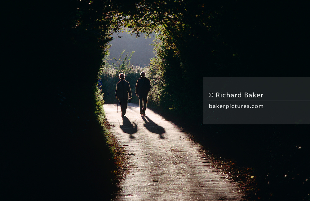 An elderly couple walk down a country lane in Burrington Combe, North Somerset.