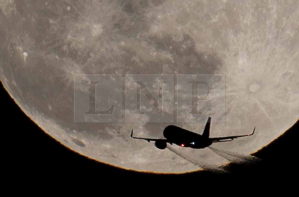 © Licensed to London News Pictures. 31/01/2018. London, UK. An aircraft heading to Heathrow passes the full blue supermoon as it rises over central London. Two full moons in the same calendar month is also know as a blue moon. Photo credit: Peter Macdiarmid/LNP
