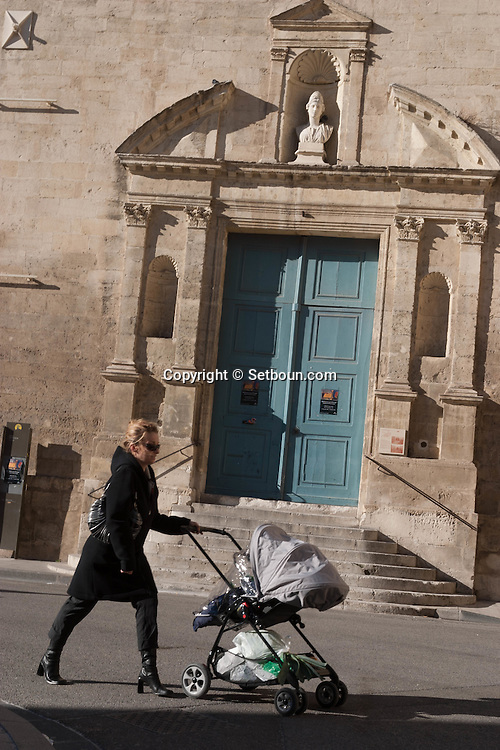 France. Bouches du Rhone.woman with a baby stroller  place de la republique in the old town of Arles