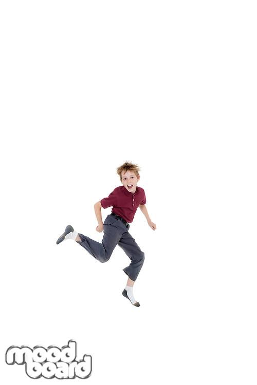 Portrait of cheerful pre-teen boy jumping over white background