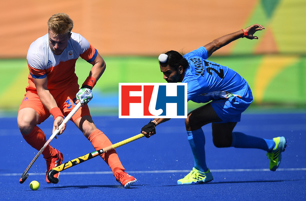 Netherland's Mink van der Weerden (L) fights for the ball with India's Akashdeep Singh during the men's field hockey Netherland's vs India match of the Rio 2016 Olympics Games at the Olympic Hockey Centre in Rio de Janeiro on August, 11 2016. / AFP / MANAN VATSYAYANA        (Photo credit should read MANAN VATSYAYANA/AFP/Getty Images)
