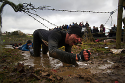 """©  London News Pictures. 27/01/2013.  A Competitor crawling underneath barbed wire as he is pushed to the limits  in the 2013 Tough Guy Challenge on January 27, 2013 in Wolverhampton, England. The event has been widely described as """"the toughest race in the world"""", with over one-third of the starters failing to finish in a typical year. Photo credit: Ben Cawthra"""