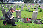 Nederland, Groesbeek, 19-7-2012Canadese militair, deelnemer aan de nijmeegse 4daagse, vierdaagse van Nijmegen, bij het graf van een gesneuvelde soldaat uit Canada op de militaire erebegraafplaats bij Groesbeek.Foto: Flip Franssen