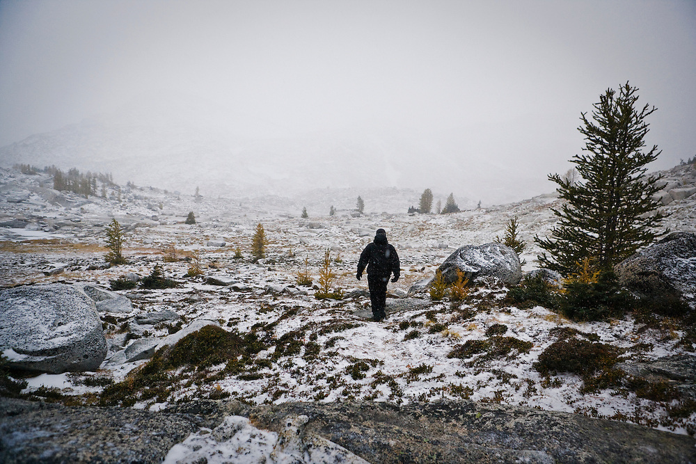 A person walking into a stormy snow covered alpine landscape, Enchantment Lakes Wilderness Area, Washington Cascades, USA.