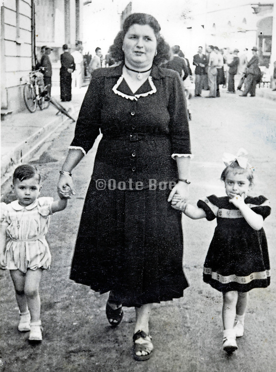 mother walking with little children on each hand Spain 1948