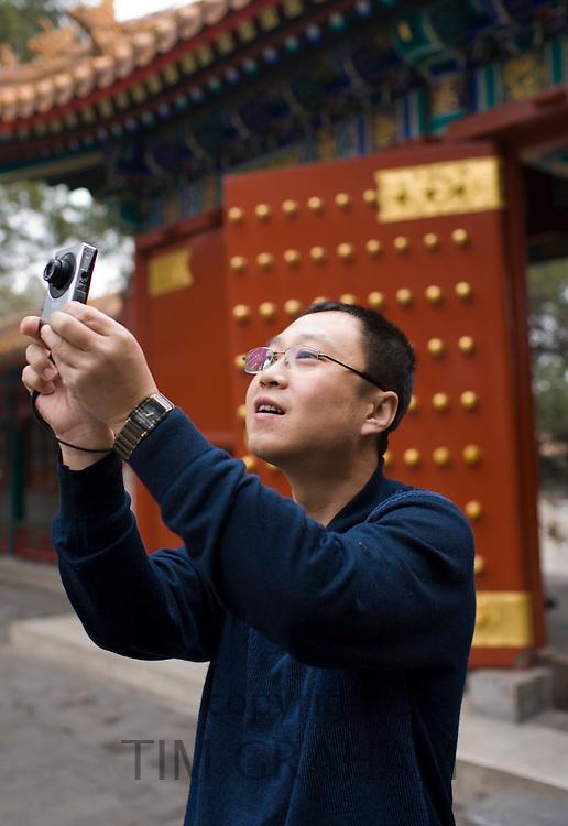 Man takes a photograph at The Summer Palace, Beijing, China
