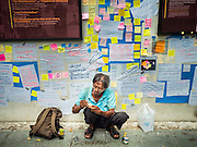 "06 JULY 2015 - BANGKOK, THAILAND:  A man carves wooden toys under a wall covered in ""Post It"" notes related to the arrest of 14 students for violating orders related to political assembly. More than 100 people gathered at Thammasat University in Bangkok Monday to show support for 14 students arrested two weeks ago. The students were arrested for violating orders against political assembly. They face criminal trial in military courts. The students' supporters are putting up ""Post It"" notes around Bangkok and college campuses up country calling for the students' release.     PHOTO BY JACK KURTZ"