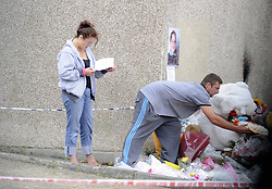 © Licensed to London News Pictures. 15/08/2012. Natalie Sharp and David Niles, parents  of Tia Sharp laying flowers at a memorial for the 12 year old on The Lindens, New Addington on August 15, 2012, as Tia's Step Grandfather, Stuart Hazell appeared at the Old Bailey by video link charged with murder. Photo credit : Grant Falvey/LNP