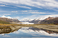 Reflection of the Alaska Range mountains surrounding the Maclaren Glacier and the Maclaren River in the Maclaren River Valley along the Denali Highway in Southcentral Alaska. Autumn. Morning.
