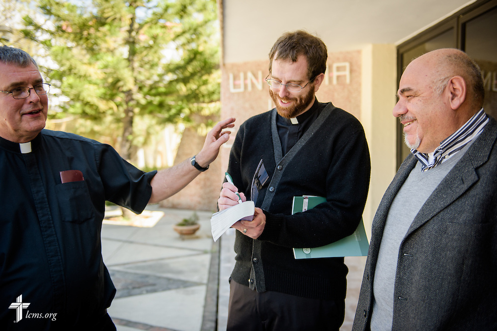The Rev. Andrew Schlund (center) and the Rev. Daniel Conrad, both LCMS missionaries to Mexico, sign a Bible for the Rev. José Ezequiel González Ayala, a Catholic priest, following a talk on Lutheranism on Friday, Jan. 13, 2017, at a Catholic Augustinian seminary in Mexico City. LCMS Communications/Erik M. Lunsford