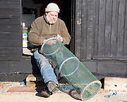 Fisherman mending lobster pot, Aldeburgh, Suffolk, England