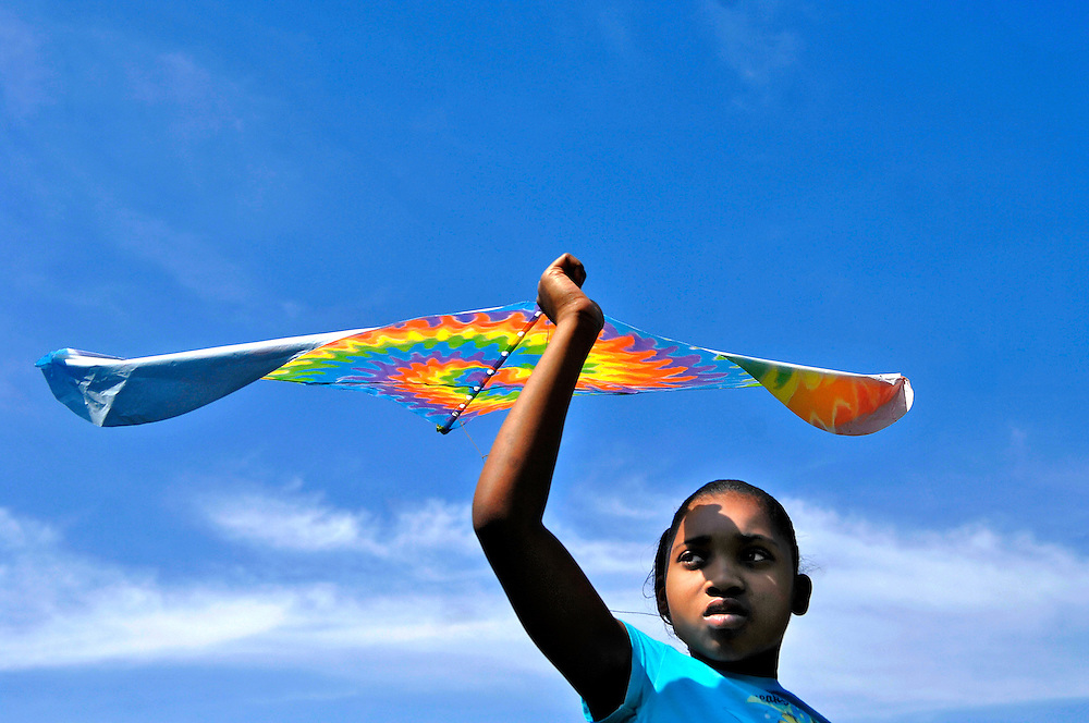 Why won't mine fly?&quot; Tynesha Green, 9, asks the skies over the Douglass Park ball field, already crowded with colorful kites.<br /> <br /> Tynesha and her sister Kanisha, 8, have come with their mentors, Amanda Koellmer and Lauren Smith, volunteers with Big Brothers Big Sisters. They have one mission: to get airborne.<br /> <br /> The first few kites are failures. Toy Story, Elmo and inflatable Winnie the Pooh all crash and burn. Tynesha jogs across the soggy field, the cuffs of her jeans muddy, her arm outstretched to release the string. Each time the kites return to earth, her spirits deflate a little more.<br /> <br /> After a consultation with a local kite-flying expert, Tynesha revives her quest with another new kite. She names it &quot;Tie-Dye&quot; for its spiral of rainbow colors. &quot;Tie-Dye, you're going to be the best flier ever,&quot; Tynesha says.<br /> <br /> Tynesha runs across the outfield, dodging younger children and jumping over kite strings. From the outfield to the infield, from the infield to the basketball courts, Tynesha is determined to fly, but the winds are not cooperating.<br /> <br /> &quot;You guys hungry? Ready to leave?&quot; Amanda asks. The girls are discouraged. They look at each other. &quot;I want to try one more time,&quot; Tynesha says.<br /> <br /> With the wind at her back she catches a breeze, and &quot;Tie-Dye&quot; lifts into the Saturday afternoon sky. Tynesha jumps. She screams. She's flying.<br /> <br /> After a short minute, &quot;Tie-Dye&quot; comes back to earth, but the girls are energized by their victory. They get a second wind, a third, a fourth and then the inevitable. &quot;Tie-Dye&quot; is caught high in the branches of a tree. As they try to retrieve it, the string snaps and the colorful kite becomes impossible to reach.<br /> <br /> Kanisha collects her own kite. Empty-handed, Tynesha follows Lauren and Amanda back to the parking lot, shedding tears for &quot;Tie-Dye,&quot; now trapped in flight forever.
