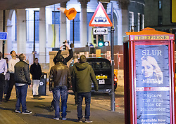 © Licensed to London News Pictures . 01/01/2015 . Manchester , UK . A man throws a traffic cone in to the air in an attempt to lodge it on an overhanging structure , on Oxford Road . Revellers usher in the New Year on a night out in Manchester City Centre .  Photo credit : Joel Goodman/LNP