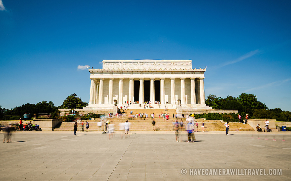 A long exposure shot of tourists visiting the Lincoln Memorial in Washington DC on a clear sunny day.
