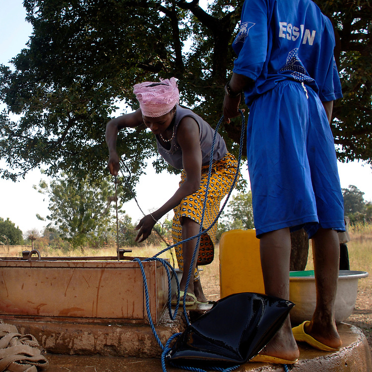 Boukoumbe December 2006 - A group of women fill water in a jerrycan by using a water well.  © Jean-Michel Clajot