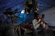Ram Kumer, 22, red/blue shirt<br /> Chandra Devdas, 38, white, Ram's uncle<br /> Displaced people from Angarpathra in Dhanbad, Jharkhand, India, light coal inside their tent on Dec 5, 2014. Forty five houses in the village collapsed as the earth caved in due to an underground coal fire on Nov 14. The government provided people who lost their homes about $200 but those who don't have money to re-build their houses live in tents.<br /> (Photo by Kuni Takahashi)