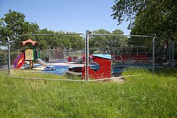 © Licensed to London News Pictures. 23/06/2020. London, UK. Overgrown grass around the playground in Chestnuts Park in north London, which has been closed and fenced since 23 March following the COVID-19 lockdown. Playgrounds will re-open from 4 July as Prime Minister Boris Johnson outlines the plans to restore normal life after three months of coronavirus lockdown. Photo credit: Dinendra Haria/LNP