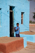 Boy leaves home in Hindu Brahman high caste village of Dhudaly heading for school in Rajasthan, Northern India