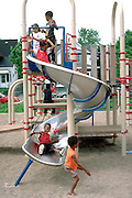Friends ages 5 and 7 playing on slide in playground.  Minneapolis  Minnesota USA