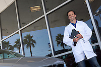 Happy car dealer standing in front of car showroom