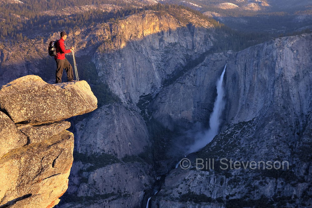 A silhouette of a man standing on an overhanging cliff at Glacier Point above Yosemite Falls in Yosemite National Park in California