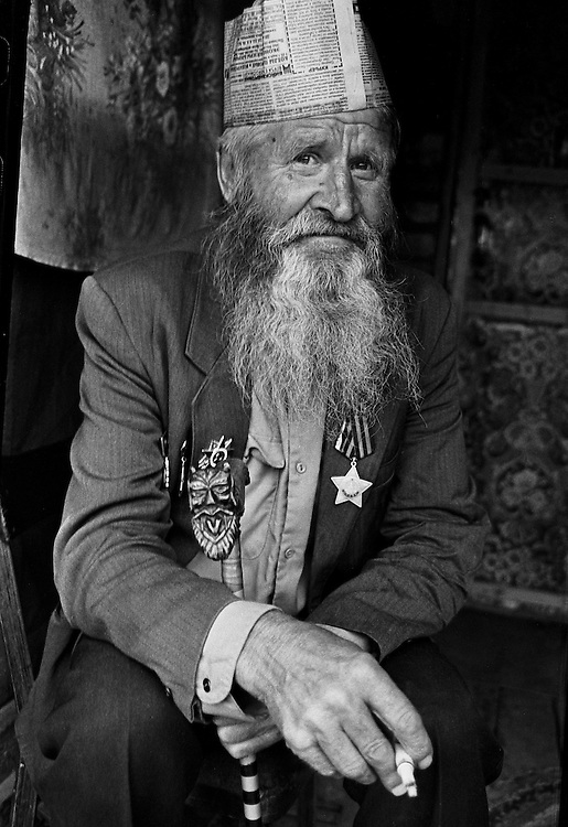 Resident of  house for an old released prisoners smokes seating near barrack where he lives in village Blagoveshenka, Kemerovo region, Eastern Siberia, Russia, 16 August 1995. Blagoveshensky house for an old former prisoners a special institution which is a part of a penitentiary system where live former prisoners which have age more then 55 years after released and haven't house or an apartment and relatives.