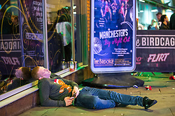 """© Licensed to London News Pictures . 24/12/2016 . Manchester , UK . A man sits slumped on the ground on Withy Grove . Revellers out in Manchester City Centre overnight during 2016's second """" Mad Friday """" , named for historically being one of the busiest nights of the year for the emergency services in the UK . Photo credit : Joel Goodman/LNP"""