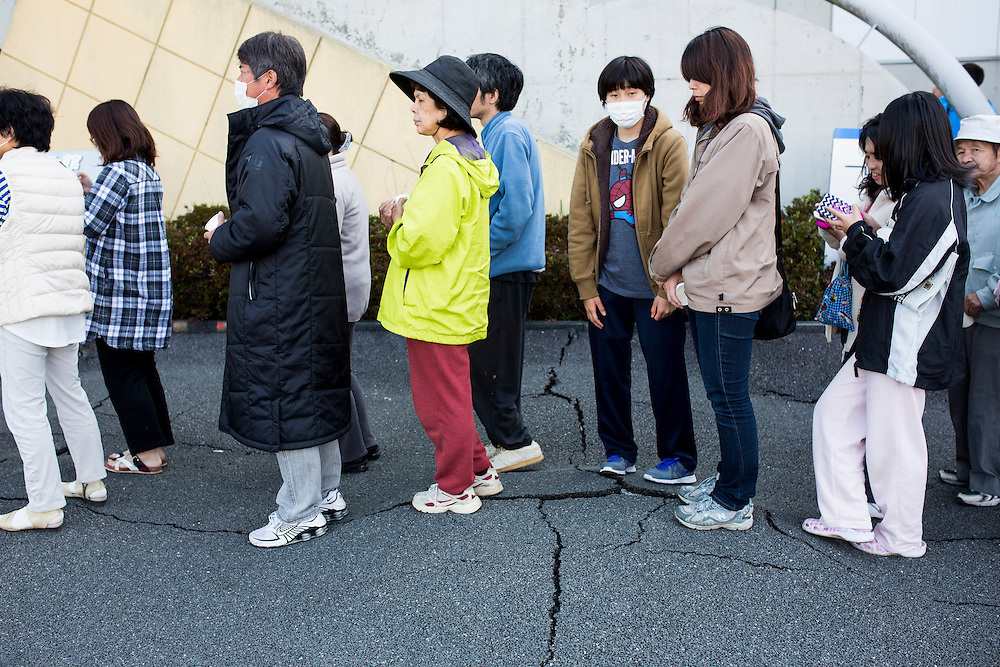 KUMAMOTO, JAPAN - APRIL 20: Evacuees line up for food distributed by Self-Defense Forces personnel early morning on Wednesday April 20, 2016 in Mashiki Gymnasium evacuation center, Kumamoto, Japan. As of April 45 people were confirmed dead after strong earthquakes rocked Kyushu Island of Japan. Nearly 11,000 people are reportedly evacuated after the tremors Thursday night at magnitude 6.5 and early Saturday morning at 7.3.<br /> <br /> Photo: Richard Atrero de Guzman